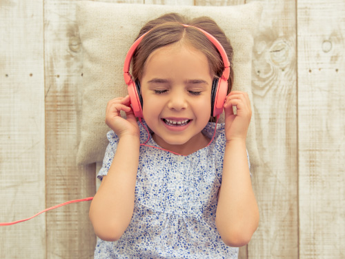 young girl listening to a song through headphones