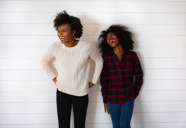 Two dark-haired young women stand against a white wall smiling and laughing while wearing long-sleeved sweaters