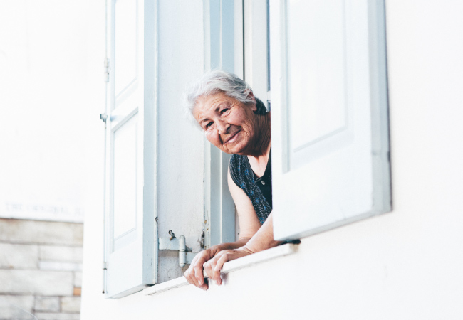 Elderly woman in need of oral care looks out the window of a white building with white shutters