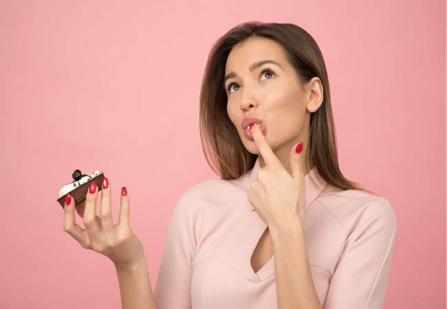 woman holding cupcake licking her finger