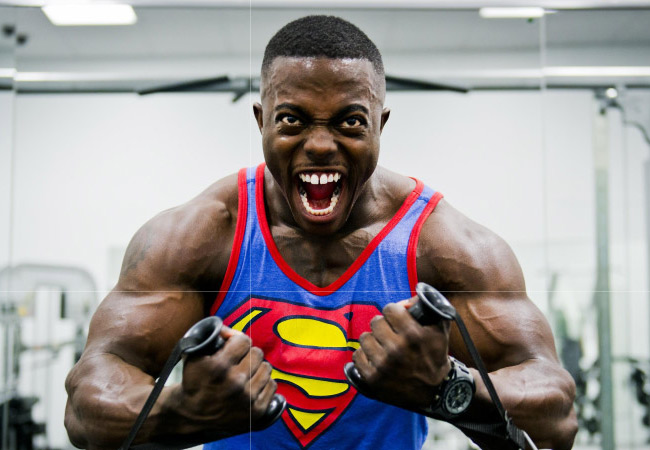 bodybuilder in superman shirt showing off his pearly white teeth